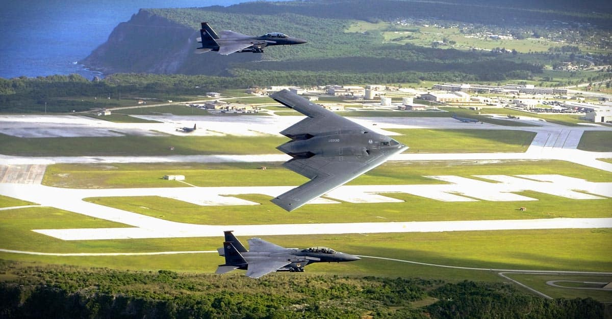 B-2_F-15E Strike Eagles and a B-2 Spirit bomber fly in formation over the base