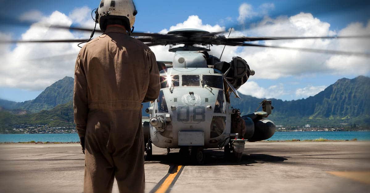 CH-53E_ helicopter crew chief communicates with flight personnel aboard a CH-53E