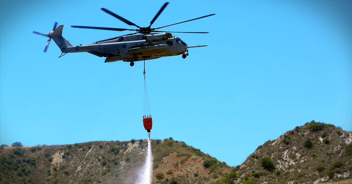 CH-53E_drops water in a mock fire area during an aerial firefighting exercise